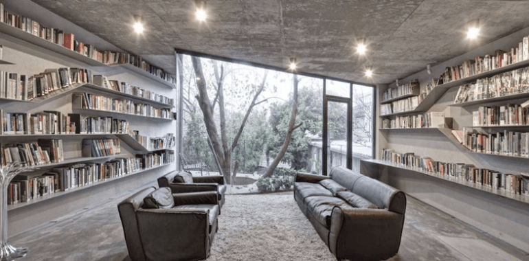 Grey home library with shelves on either side of the room and two sofas facing each other in the middle, with large window in the background