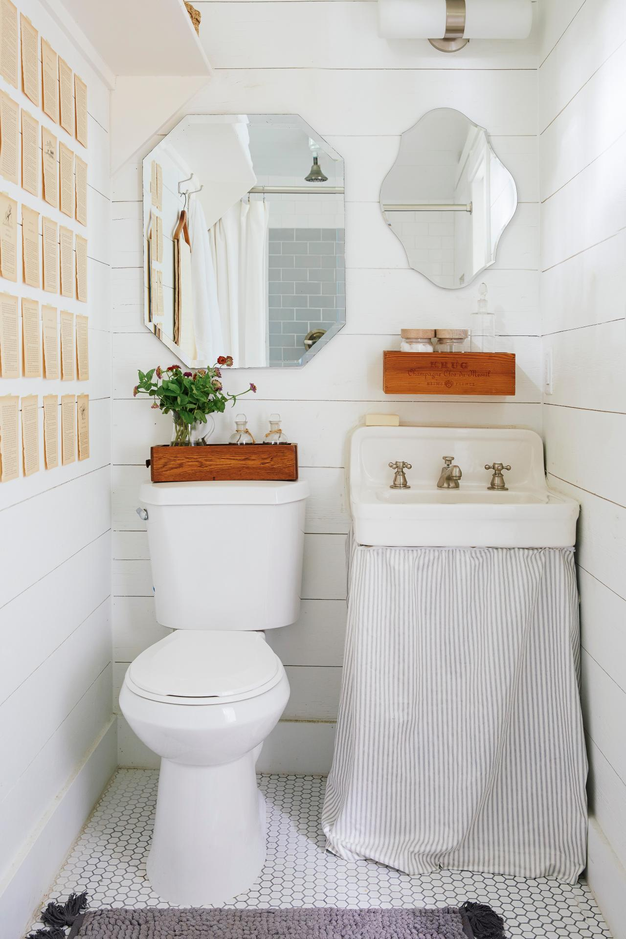 A small white bathroom with pages from a book stuck on the wall