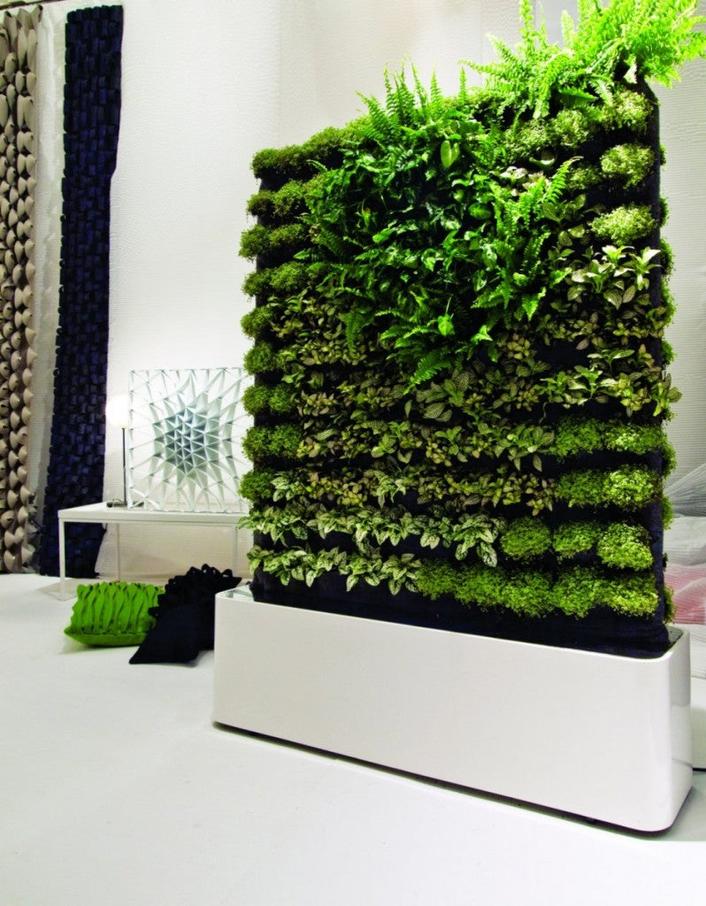 A white planter containing a tall column of green plants and moss