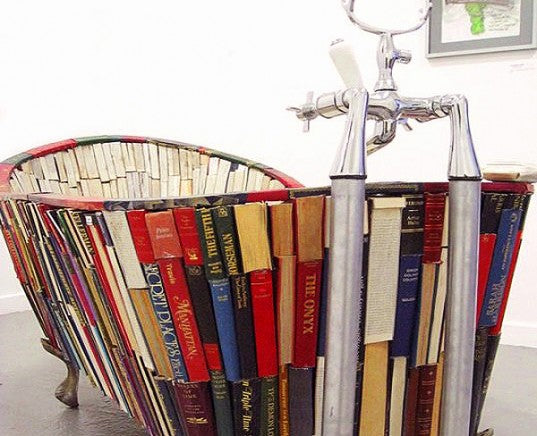 A bathtub with the spines of books used to decorate the outside of the tub