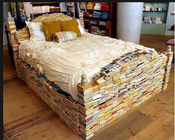 A double bed made from books, which are stacked and glued together to make a bed frame