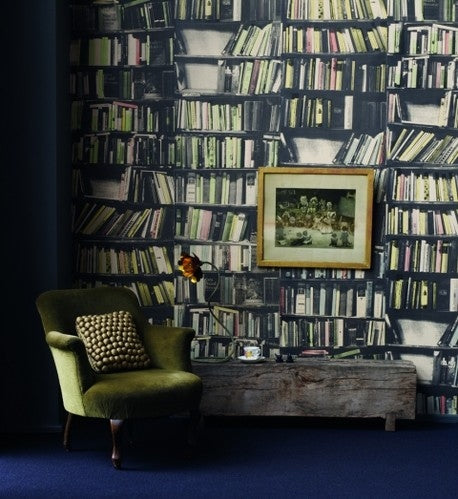 Dark green reading chair, with wallpaper on the wall that looks like lots of books on bookshelves