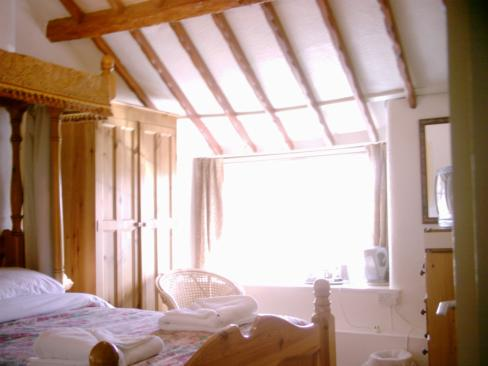 Sloping roof with exposed wood beams, above a bright bedroom window style=