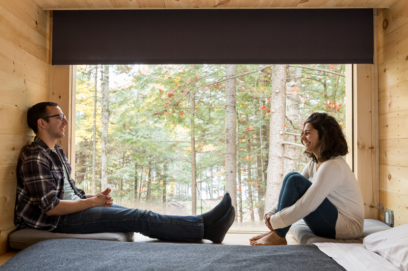 Two people sitting next to a window in a small wooden eco bedroom
