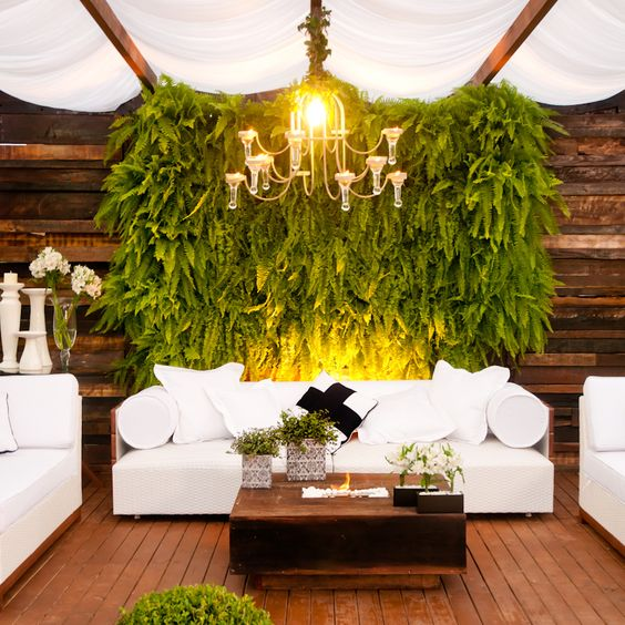 Lots of greenery and plants on a wooden panel wall, set behind white sofas