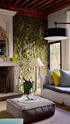 A green moss wall in a stylish living room, next to a white fireplace