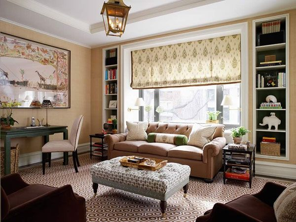 Beige living room with patterned roman blind in front of a large window