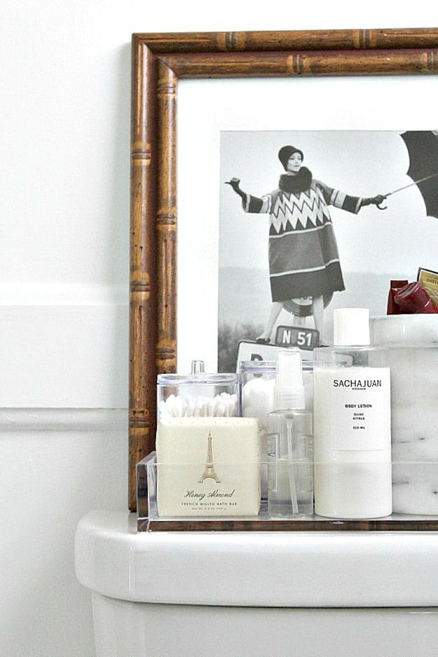 Toiletries displayed on a toilet, as well as wooden framed black and white photo