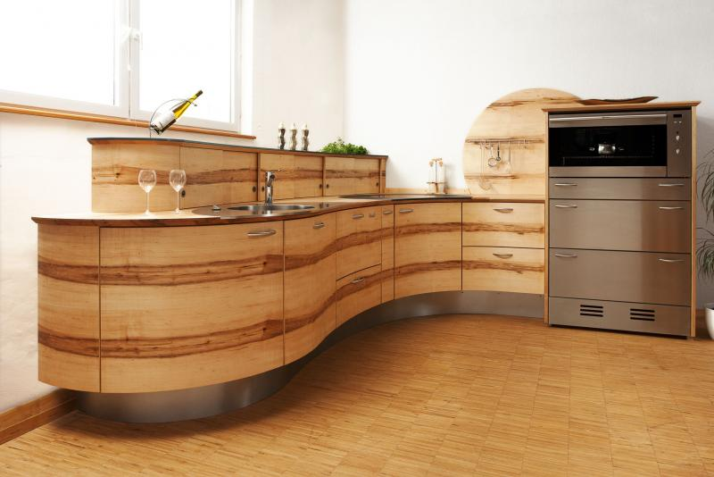 Natural wooden kitchen units with a curved finish in a white kitchen, with silver metallic oven