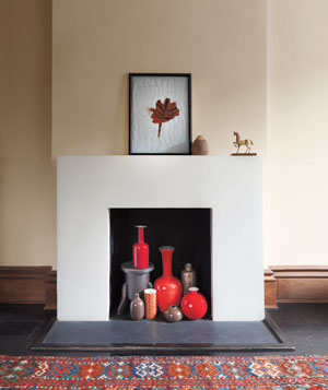 White and cream fireplace with red, brown and grey vases in the hearth