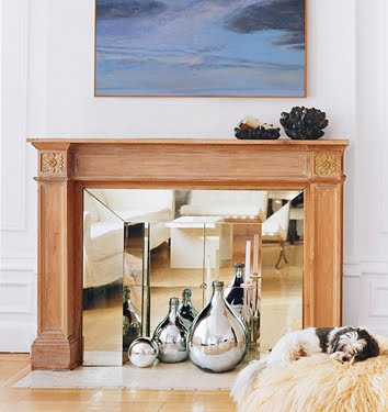 White living room with wooden fireplace and the surround and hearth covered in mirrors