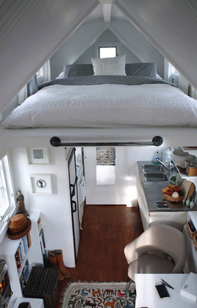 A double bed suspended in the rafters on a small eco-home