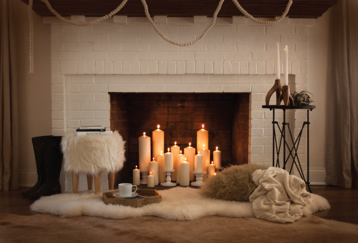 Cream brick fireplace with lots of candles in the hearth and cream and beige rug on the floor