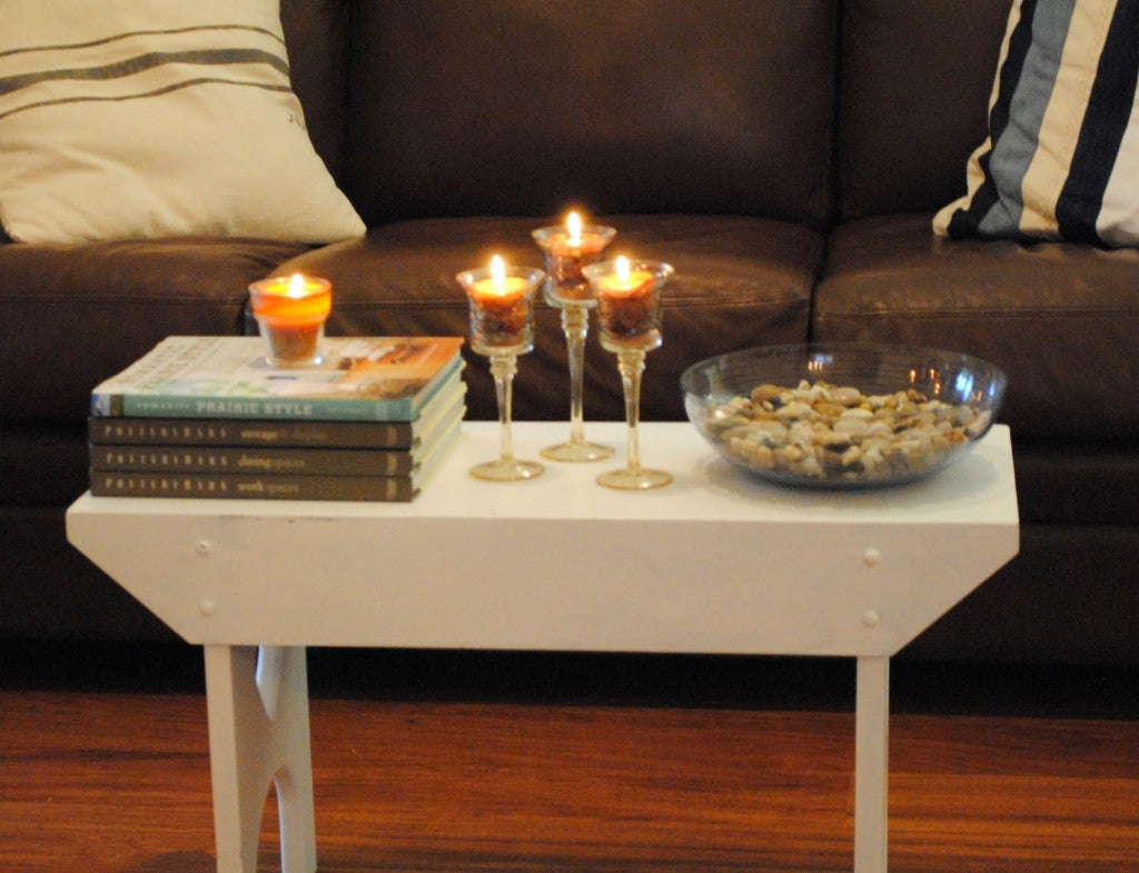 Books and candles on a coffee table, in front of a leather sofa
