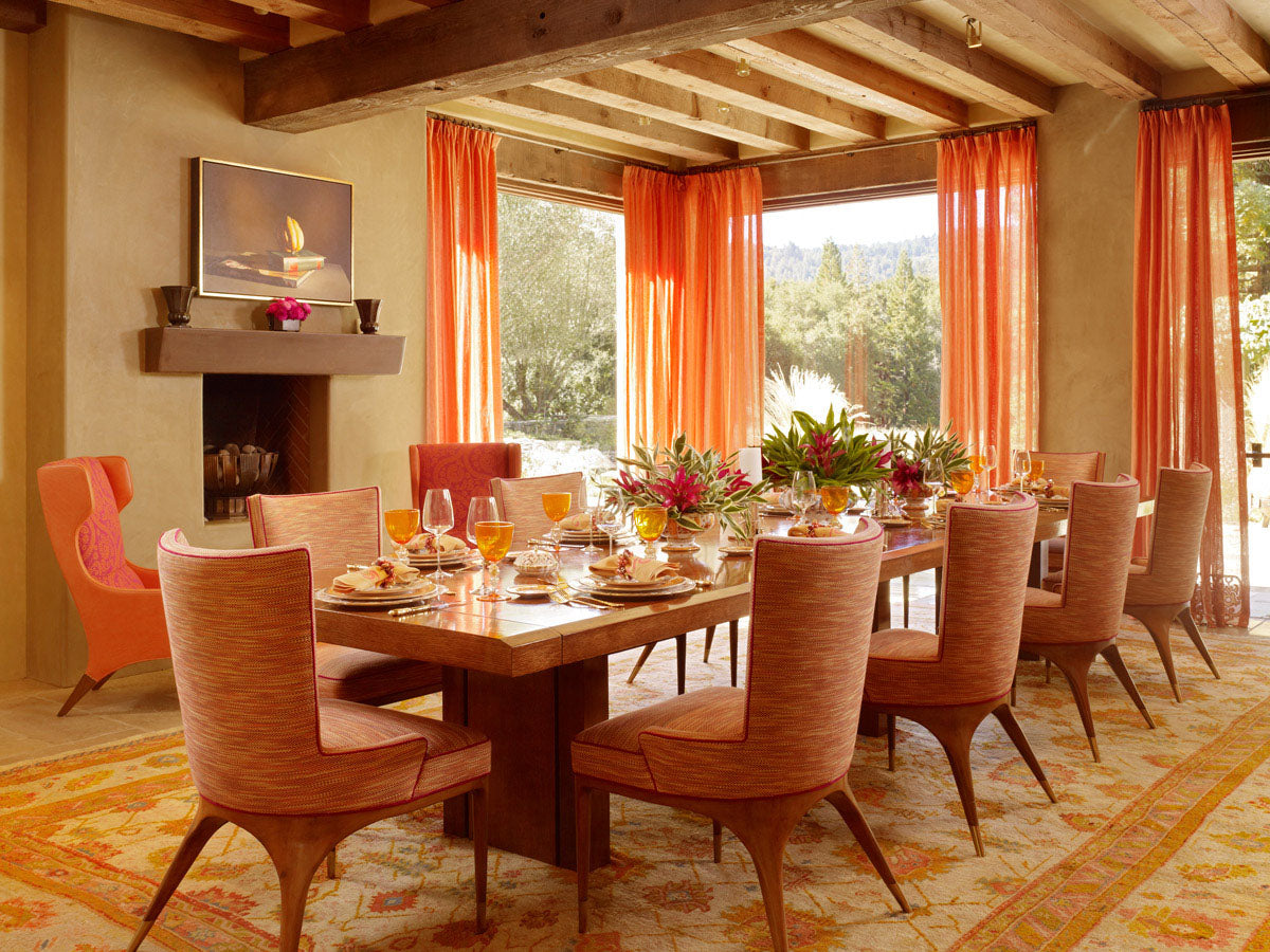 Orange and peach dining room with large floor to ceiling windows and veranda doors