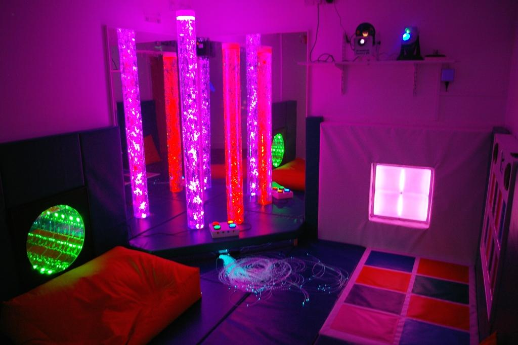 Purple, red and green lights in a dark sensory room