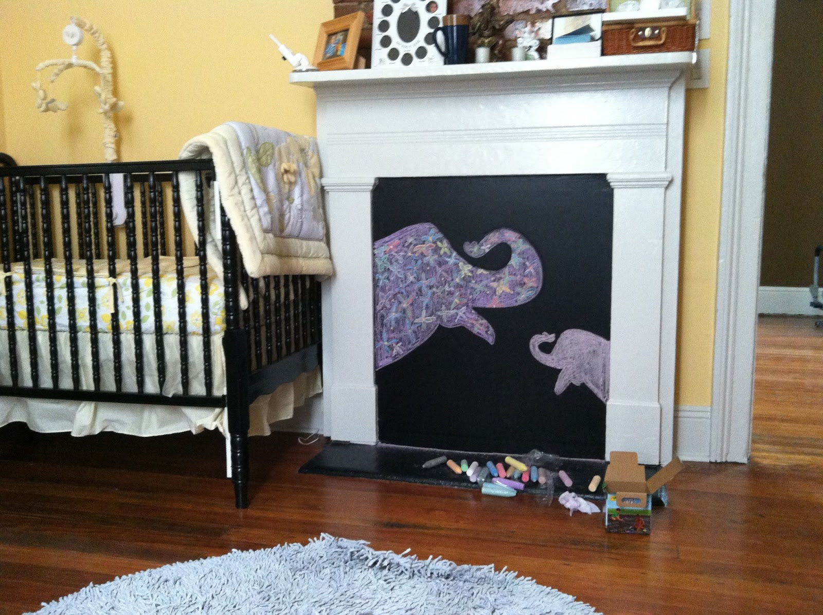 Yellow nursery with black cot and a black chalkboard covering the fireplace, with baby and mummy purple elephants chalk drawing