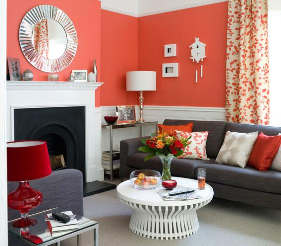 Red, orange and peach living room with grey sofa and armchair