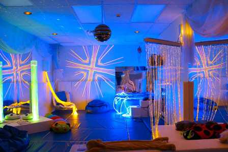 Sensory room with dark blue lighting and patterned neon accessory lights