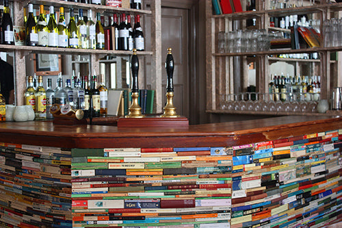 A pub with the side of the bar covered in the spines of hundreds of different books