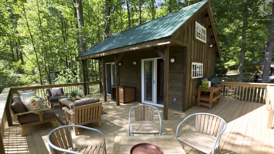 Lovely wooden home in the woods, surrounded by wooden decking and seating area