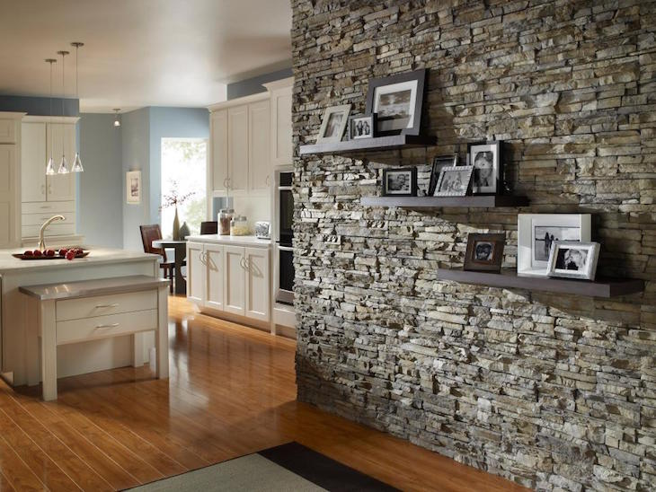 Stone clad kitchen wall with three floating shelves