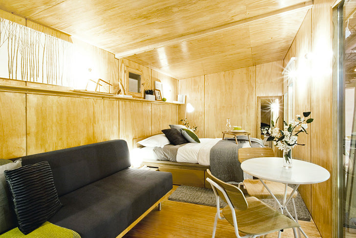 Small wooden room with bed and sofa, looks like the inside of sauna