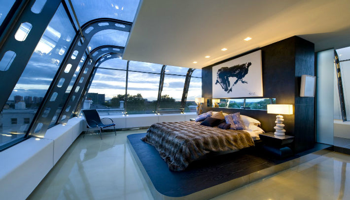 A stylish bedroom with very large windows that stretch onto the roof, resembles a large old fashioned plane cockpit
