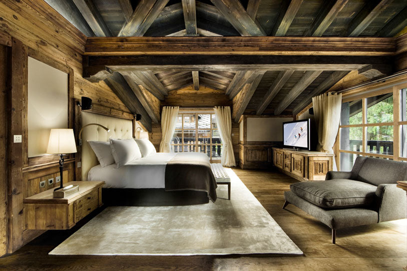 Log cabin bedroom with lots of exposed wooden beams and bed, TV cabinet and comfy brown arm chair