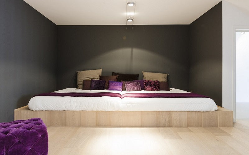 Grey and cream bedroom with very wide white bed, with purple, brown and beige accent colours