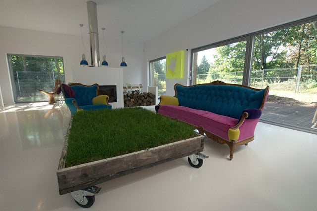 Indoor Grass Planter On Industrial Wheels Positioned In Front Of A Pink Sofa