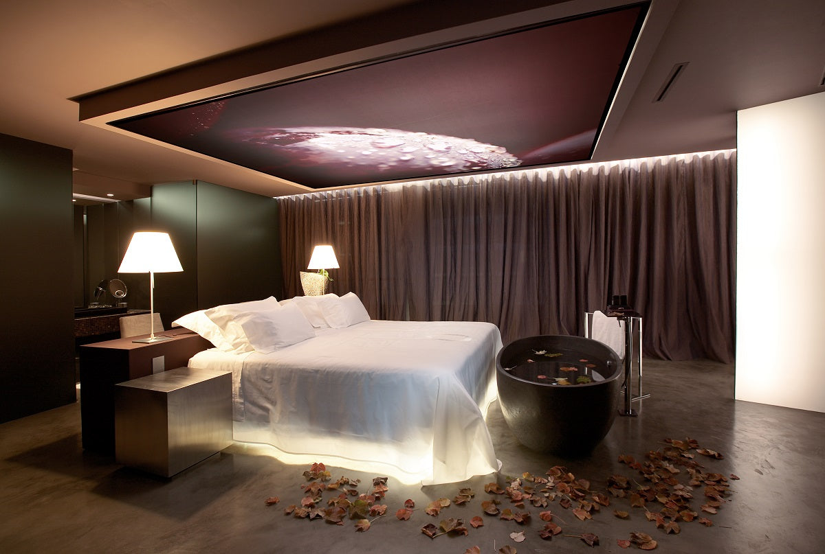Luxury bedroom with large TV screen on the ceiling, with a purple, brown and beige colour scheme
