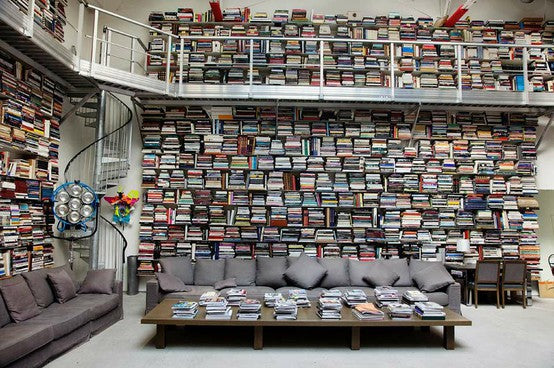 Hundreds of shelves on two floors with an industrial metal balcony and dark grey sofas on the ground floor