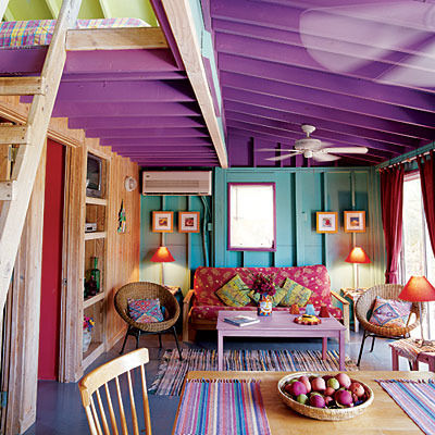 Purple and teal loft wooden beam living space with red sofa and dining table