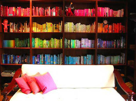 Book shelves with books arranged by colour, with red on top shelf, yellow, then green and blue on the bottom shelf