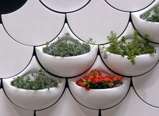 Wall with white tiles in a scale like design, with protruding containers containing plants and herbs