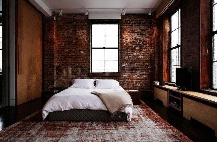 White bed in an urban style bedroom with exposed brick walls