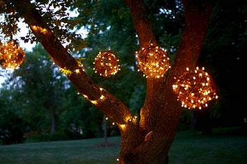Fairy light balls hung from a garden tree at dusk