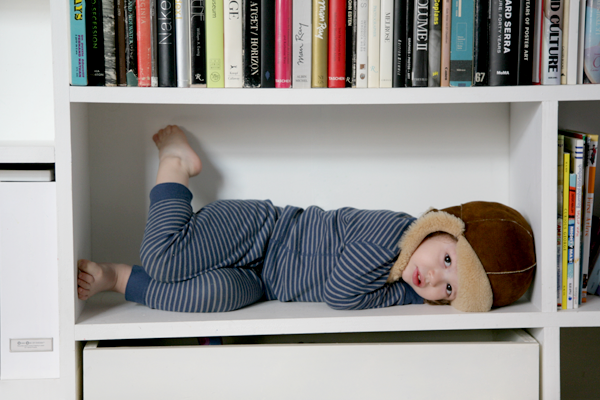 A young child in pyjamas lying within a white bookshelf