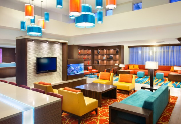 Orange and teal large living that looks like a hotel reception