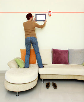Man standing on a sofa straightening up a picture frame