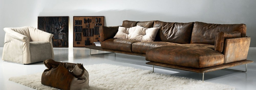 Brown leather corner sofa with cream cushions, and cream armchair