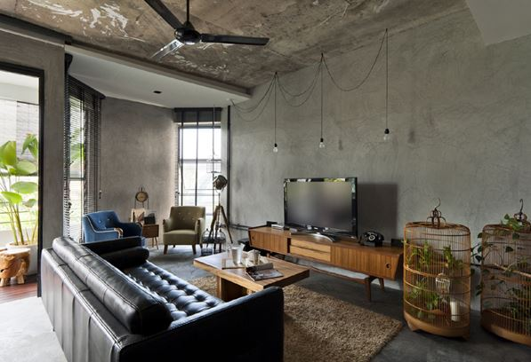 An industrial style exposed concrete living room with black leather sofa