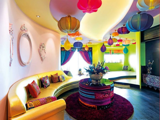 Curved wall living space with curving orange sofa and lots of coloured ceiling lanterns