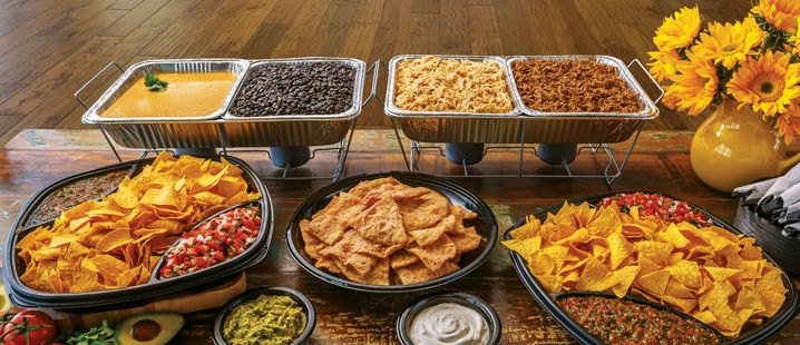 Food buffet of nachos and different dips