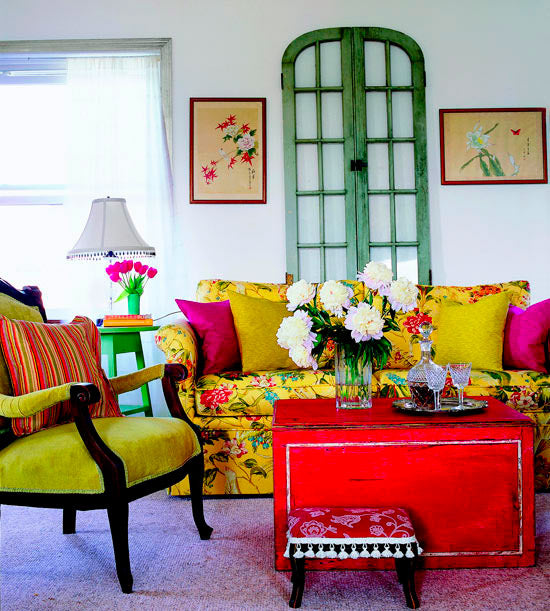 Colourful living room with yellow sofa, green arm chair and red box coffee table