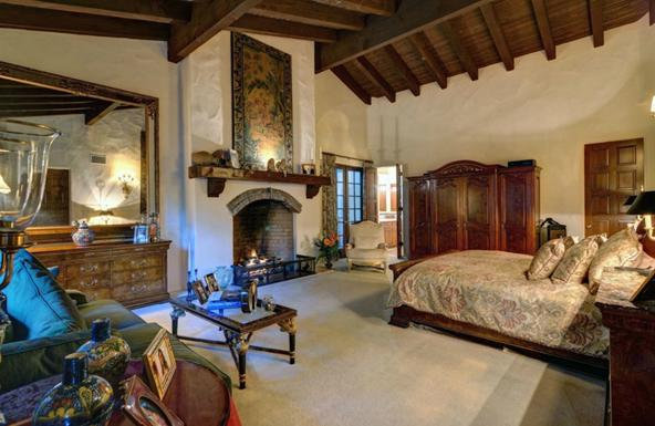 Luxury cabin style bedroom with cream walls and floors, lots of dark wooden furniture and exposed ceiling beams
