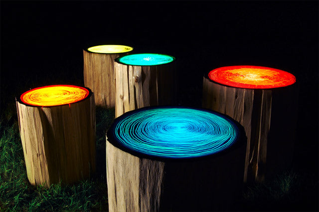Funky summer garden lights that look like tree trunks with glowing tops in different colours