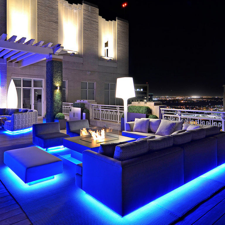 Outdoor seating area and fire feature on the table top, illuminated with bright blue lights under all of the chairs