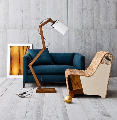 Grey wood panel floors and walls with dark blue two seater sofa and modern wooden armchair